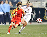 Carli Lloyd #10 of the USA WNT holds onto Yuan Xu #8 of the PRC WNT during an international friendly match at PPL Park, on October 6 2010 in Chester, PA. The game ended in a 1-1 tie.