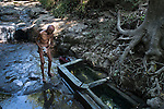 """November 09, 2014. """"Water it´s the real thing""""<br /> Felipe Ruiz, 65 years old, washes himself in a place called El Caballo with contaminated water. He doesn' t have water at home and he has to walk near two hours to El Caballo. The people of Nejapa in El Salvador, have no drinking water because the Coca -Cola company overexploited the aquifer in the area, the most important source of water in this Central American country. This means that the population has to walk for hours to get water from wells and rivers. The problem is that these rivers and wells are contaminated by discharges that makes Coca- Cola and other factories that are installed in the area. The problem can increase: Coca Cola company has expansion plans, something that communities and NGOs want to stop. To make a liter of Coca Cola are needed 2,4 liters of water. ©Calamar2/ Pedro ARMESTRE"""