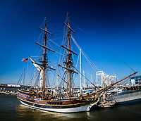 A vintage ship, the tall ship Lady Washington, moored at Jack London Square, Oakland, its dual masts and intricate rigging rise into a clear blue sky.