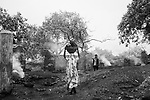 A lady carries pilfered coal to her home to sell it in the black market, Jharia, Jharkhabd, India.