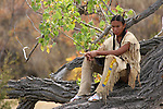 A teenage Native American Indian boy sitting on a downed tree