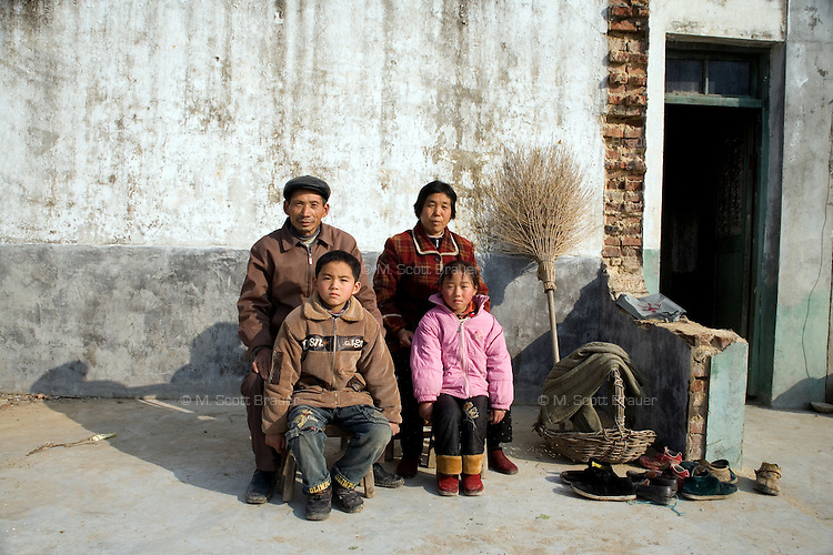 The orphans Zhao Min, 9, and brother Zhao Shi, 6, pose for a picture with their grandparents outside their home in Qingdun Village, Gangyun County, Jiangsu, China, as grandmother Sun Zhan Xia looks on.  The orphans have lived with their grandparents Sun Zhan Xia (female) and Zhao Xia You (male) since 2007 when the children were orphaned in 2007. The children's father, Sun Zhan Xia's son, died of hepatitis in 2006 and their mother was forced to remarry and abandon the children in 2007.  Sun Zhan Xia and her husband are both over 60 and in bad health.  The couple owes approximately 40,000 RMB (about $5,300 USD) to pay for the medical treatment of their dead son, the children's father.  Due to their health situation and this enormous debt, the pair cannot afford to care for the children any longer, and the children are in danger of being placed in orphanages.  ..At the time of the picture, China's Amity Foundation charity, was investigating the family's situation in preparation to raise money to financially support these children and other orphans in similar situations.  With Amity's support, each orphan, aged 6-12, would receive approximately 1,400 RMB annually (about 200 USD) to pay for the cost of living. Amity works to keep children out of the institutional orphanages in China, preferring to provide monetary assistance that can help maintain a family environment for the orphans it helps.