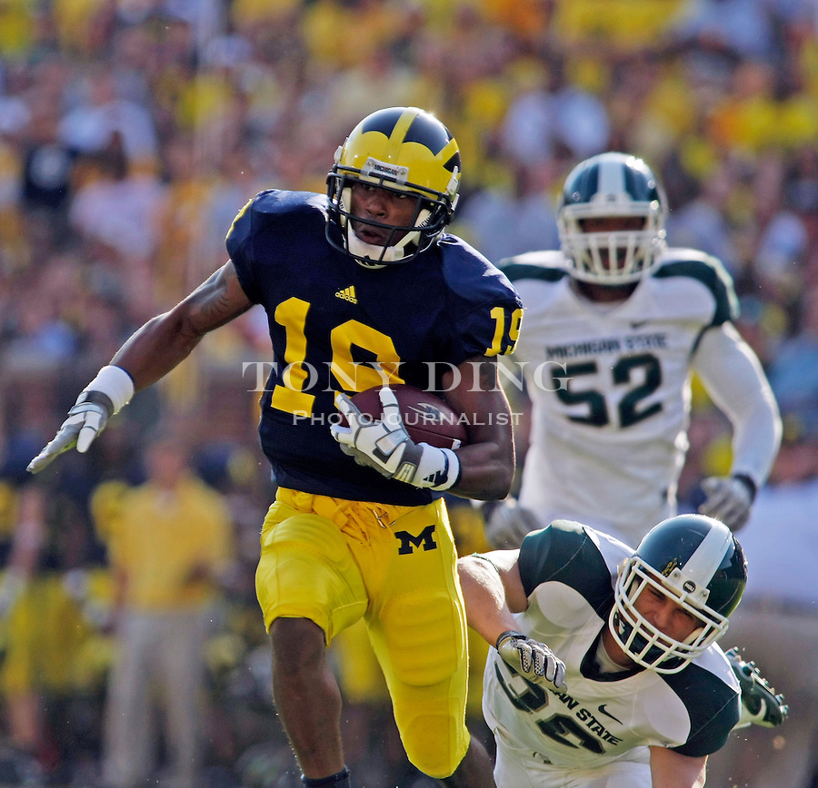 Michigan wide receiver Kelvin Grady (19) rushes away from Michigan State defensive end Denzel Drone (52) and linebacker Jon Misch, bottom, in the second quarter of an NCAA college football game, Saturday, Oct. 9, 2010, in Ann Arbor, Mich. (AP Photo/Tony Ding)