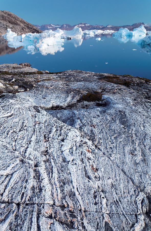 Icebergs and glacier polished bedrock at dusk along Sermilik Fjord near settlement of Tiniteqilaq, East Greenland
