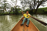 A Mayan boy paddles his dugout canoe on the river nea his village, Crique Sarco, in southern Belize.