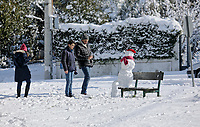 Pictured: A young family take a picture of a snowman in the Kastri area of Athens, Greece. Tuesday 08 January 2018<br /> Re: Heavy snowfall has affected most parts of Greece.