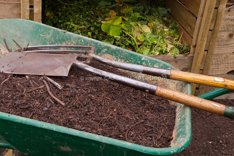 Compost Bin and Wheelbarrow of composted materials to add to the garden with shovel, fork tools