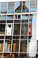The reflected image of an old building, the store Félix Potin that is now an historical monument, in rue the Rennes, onto the glass wall and the colored mirror windows of a building in the other side of the road, with a street lamp (Paris, 2010).<br /> <br /> L'immagine riflessa di un vecchio edificio, il magazzino Felix Potin che è ora un monumento storico, in rue de Rennes, sulla parete di vetro e le finestre a specchio colorate di un edificio dall'altra parte della strada, con un lampione (Parigi, 2010).
