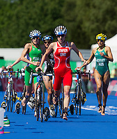 24 JUL 2014 - GLASGOW, GBR - Jodie Stimpson (ENG) (centre, in red and white) from England leads the way through transition at the end of the bike during the elite women's 2014 Commonwealth Games triathlon in Strathclyde Country Park, in Glasgow, Scotland (PHOTO COPYRIGHT © 2014 NIGEL FARROW, ALL RIGHTS RESERVED)<br /> *******************************<br /> COMMONWEALTH GAMES <br /> FEDERATION USAGE <br /> RULES APPLY<br /> *******************************