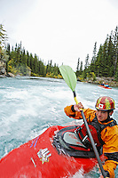 Andrew Jobe paddling whitewater kayak at the Widow Maker rapid on the Kananaskis River, Kananaskis County, Alberta, Canada
