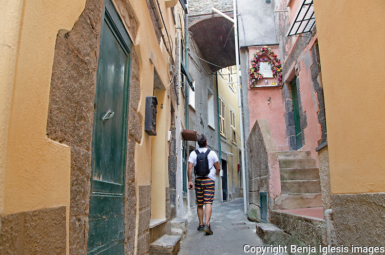 A tourist walking around the labyrinth of alleys in the town of Vernazza.