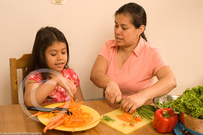 8 year old girl with mother in kitchen cooking cutting vegetable carrot interaction talking