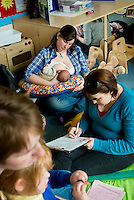 """A mother breastfeeding her baby at a drop-in breastfeeding support centre while the breastfeeding consultant takes some notes from another mother.<br /> <br /> Image from the """"We Do It In Public"""" documentary photography project collection: <br />  www.breastfeedinginpublic.co.uk<br /> <br /> Dorset, England, UK<br /> 17/04/2013"""