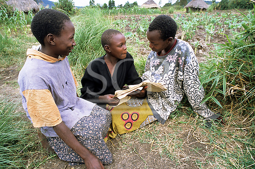 Lolgorian, Kenya. Three girls sitting on the ground reading from a tattered text book, doing their homework.