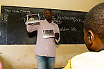 African Golden Cat (Caracal aurata aurata) researcher, Sam Isoke, giving lecture in primary school, part of an educational activity to teach children about forest animals, western Uganda