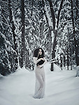 Beautiful woman in white long dress walking in the snow with a black cat in her hands in winter nature scenery Image © MaximImages, License at https://www.maximimages.com
