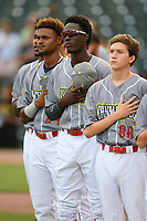 Members of the Columbia Fireflies, including Ronny Mauricio (center), stand for the National Anthem before a game against the Charleston RiverDogs on Friday, July 12, 2019 at Segra Park in Columbia, South Carolina. The RiverDogs won, 4-3, in 10 innings. (Tom Priddy/Four Seam Images)