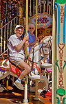 Senior couple, 85 years old, riding on a carousel.<br />