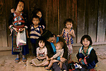 Hmong mother outside her village home with her seven children. Village called Pa Kludy, Northern Thailand South East Asia 1990s