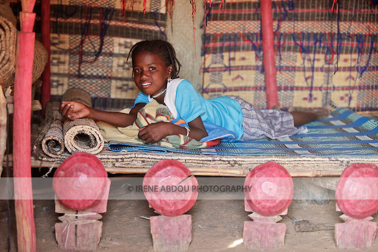 In the Fulani village of Jolooga in northern Burkina Faso, a girl sits on a traditional bed in a house made of handwoven straw mats supported by thin sticks of wood.  Additional straw mats serve as a mattress.