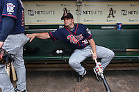 OAKLAND, CA - JULY 22:  Brian Buscher #32 of the Minnesota Twins grabs the pants of teammate Nick Punto #8 in the dugout before the game against the Oakland Athletics at the Oakland-Alameda County Coliseum on July 22, 2009 in Oakland, California. Photo by Brad Mangin
