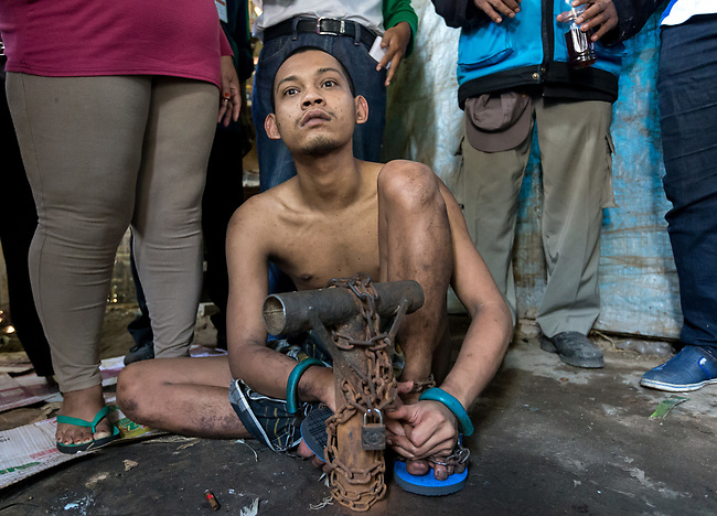"""5 April 2017, Surabaya,East Java,Indonesia: Febrianto, a 24 year old mental illness sufferer prepares to be released from the chains he has been shackled to a stake for the past two years in a goat shed next to his family in Pehwetan village, East Java. His mother Barokah, looks on (legs at left) as Indonesian Social Affairs Dept. workers cut the bonds and wash his emaciated body and apply first aid before putting him in a straight jacket and taking him to a facility in Malang for treatment. Febrianto is a patient in a program called """"E- Shackling"""" which aims to free people suffering from mental illness, from the shackles that family often place them in to control them in the wake of a lack of treatment options and which will treat them and enter them in a data base allowing them to be traced before releasing them back to their families. Some people stay chained to a stake or in rooms for years by their families and not all families are willing to take their sick family members back. Picture by Graham Crouch/The Australian"""