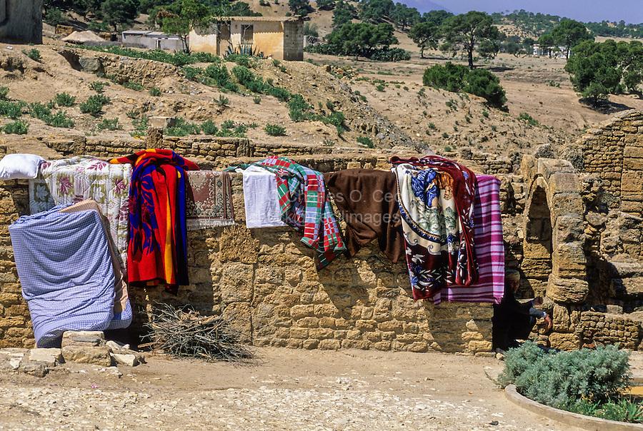 Tunisia, Le Kef.  Hammam Mellegue, Roman Era Baths, Roman Arch on Right.  Rugs, Bedding Airing in the Sunlight.