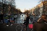 People cross the Berenstraat bridge over the Prinsengracht in downtown Amsterdam.