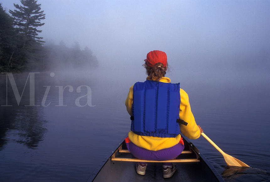 canoeing, canoe, Vermont, VT, Woman paddling a canoe on Kettle Pond in the fog in Groton State Forest.
