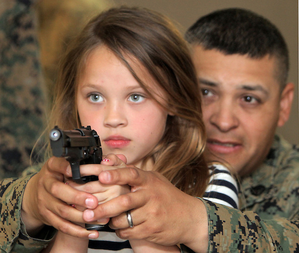 "X.work.1.0309.jl.jpg/Jayden Orrante of Oceaside takes aim with her father Marine Staff Sgt. Ernie Orrante's help while shooting in  an Indoor Simulation Markmanship Training room held Camp Pendleton's Alpha Company Barracks Friday during ""Bring your child to work Day.  JAMIE SCOTT LYTLE 