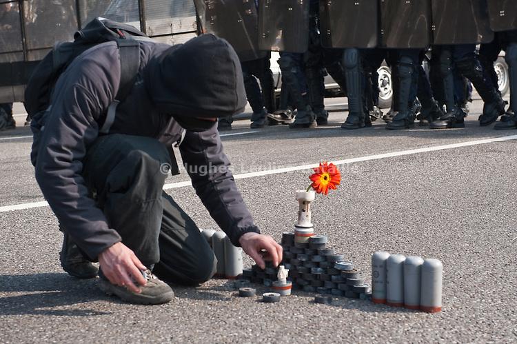"""Un membre des """"Black Blocks"""" met la touche finale a une pyramide consituee des differents types de grenades lancees par les forces de l'ordre, alors que celles-ci s'avancent sur le pont Vauban menant au port autonome de Strasbourg. Le pont sera le theatre de violents accrochages pendant plus de 2 heures avant la manifestation du 4 avril 2009 contre le sommet de l'OTAN, la police repondant par des grenades lacrymogenes et assourdissantes aux jets de projectiles (pierres, bouteilles, cocktails molotov)..Credit;Hughes Leglise-Bataille/Julien Muguet/face to face"""