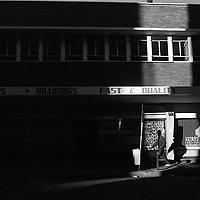A man walks past a hairdresser's salon in Kruis Street, Marshaltown.