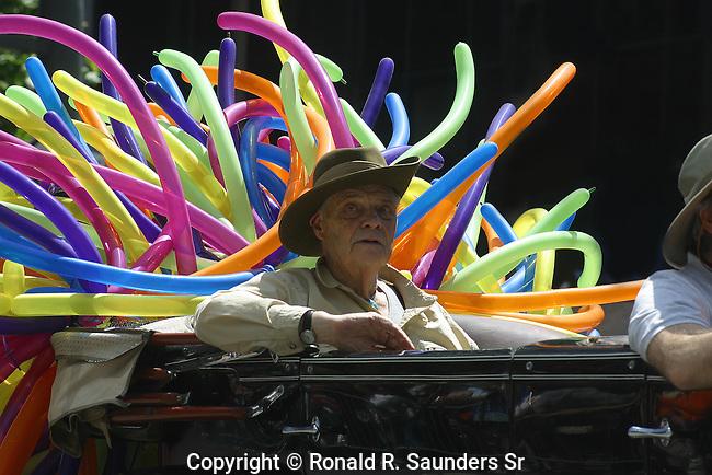 ELDERLY MAN RIDES IN BALLOON DECORATED CONVERTABLE