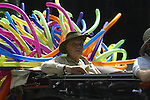 ELDERLY MAN RIDES IN BALLOON DECORATED CONVERTABLE