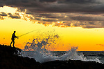 Silhouette of Fisherman on the rocks at Stockton Beach, Anna Bay, NSW, Australia