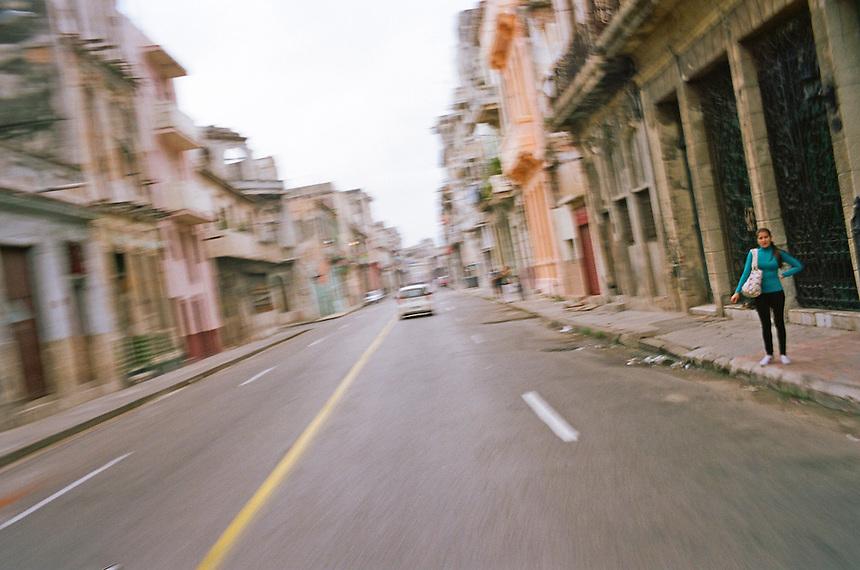 A woman waits for a ride on Old Havana, Cuba. MARK TAYLOR GALLERY