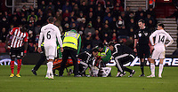 Pictured: Modou Barrow of Swansea injured on the ground is seen by his team's physio and doctor before stretchered off Sunday 01 February 2015<br />