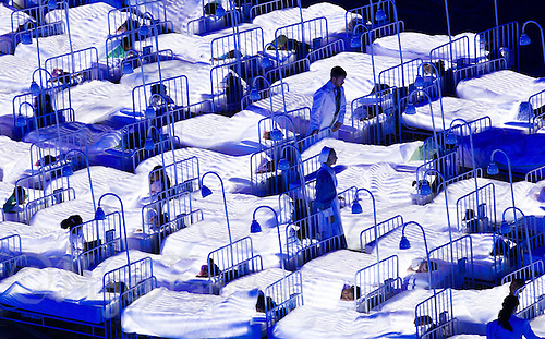 """27 JUL 2012 - LONDON, GBR - A doctor and nurse walk between the beds of sleeping children during the """"Second To The Right, And Straight On Till Morning"""" section of the Opening Ceremony of the London 2012 Olympic Games in the Olympic Stadium in the Olympic Park, Stratford, London, Great Britain .(PHOTO (C) 2012 NIGEL FARROW)"""