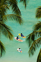 Young surfers framed by palm trees head out to catch the perfect wave in the warm, blue waters off beautiful Waikiki Beach,Oahu.
