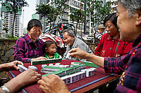 75 year old Ran Shunbi plays mahjong while holding her three year old great-grandson at their relocation housing in the southwestern Chinese megapolis of Chongqing. She and her extended family were moved from their farmland and resettled nearby in this purpose-built estate. The middle generations are at work in the city. The Chinese government plans to move 250 million rural residents into urban areas over the coming dozen years though it is unclear whether people want to move and where the money for this project will come from. Further urbanisation is meant to drive up consumption to counterbalance an export orientated economy and end subsistence farming but the drive to get people off the land is causing tens of thousands of protests each year. /Felix Features