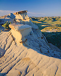 Theodore Roosevelt National Park, ND: Morning light on eroded bentonite ridge overlooking badland hills