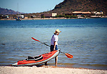 Man hauls kayak out to the Bay of Conception<br /> <br /> A kayak is a small boat resembling an Eskimo canoe and made commercially of a variety of materials and used in sports