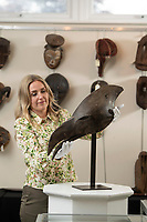 BNPS.co.uk (01202) 558833.<br /> Pic: BNPS<br /> <br /> PICTURED: Zoe Cordey from Woolley & Wallis with an eye-catching 25ins Chokwe bird head mask originating from Angola<br /> <br /> A remarkable assortment of African and Oceanic artefacts are being sold at a British auction house.<br /> <br /> The rare relics, which have come from several prominent private collections, include tribal weapons, figures and masks.<br /> <br /> They are going under the hammer with auctioneers Woolley & Wallis, of Salisbury, Wilts.<br /> <br /> The marquee lot is an exquisite 19th century Polynesian 4.5ft-long war club valued at £30,000.<br /> <br /> Also up for grabs is an eye-catching 25ins Chokwe bird head mask originating from Angola with a modest estimate of £800. A wooden 30ins standing male figure from the Bay of Bengal, India, which was carved to ward off evil spirits could fetch £3,000.