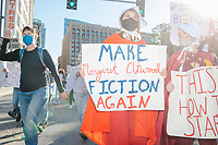 """Protestors, including some dressed in the red cloaks of The Handmaid's Tale, march along Tremont Street as they make their way to Boston City Hall during the 2020 Women's March protest in opposition to the re-election of US president Donald Trump in Boston, Massachusetts, on Sat., Oct. 17, 2020.<br /> The signs here read """"Make Margaret Atwood Fiction Again"""" (a reference to the dystopian novel The Handmaid's Tale) and """"This is how it starts."""""""