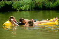 Summer fun in the lake: Kids playing in pond stop to rest on mom