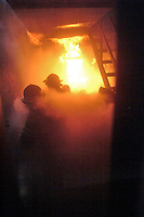 Firefighters surrounded by smoke attack a kitchen fire inside the fire training burn trailer during training with the Occidental Volunteer Fire Department.