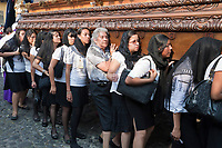 Antigua, Guatemala.  Semana Santa (Holy Week).  Concentration  shows on the faces of women carrying an anda (float) in a procession during Holy Week.