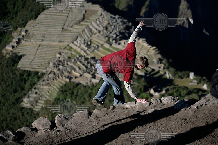 A young man fakes a fall from Huayna Picchu (Wayna Picchu) a site high above Machu Picchu, the so-called 'Lost City of the Incas'. Each day hundreds of tourists wait outside of the ruins of Machu Picchu but only the first 400 people to arrive at the site get to climb to Huayna Picchu..
