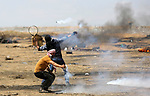 A Palestinian protester uses a racket to throw back a tear gas canister fired by Israeli security forces during clashes in tents protest where Palestinians demanding the right to return to their homeland, at the Israel-Gaza border, in Khan Younis in the southern Gaza Strip, on May 11, 2018. Photo by Ashraf Amra