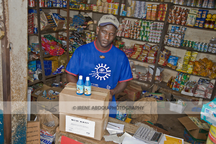 """A wholesaler in Conakry, Guinea logs in bottles/boxes of """"Sur'Eau,"""" a chlorine product that makes water safe to drink.  Sur'Eau is distributed by the international social marketing organization, Population Services International."""